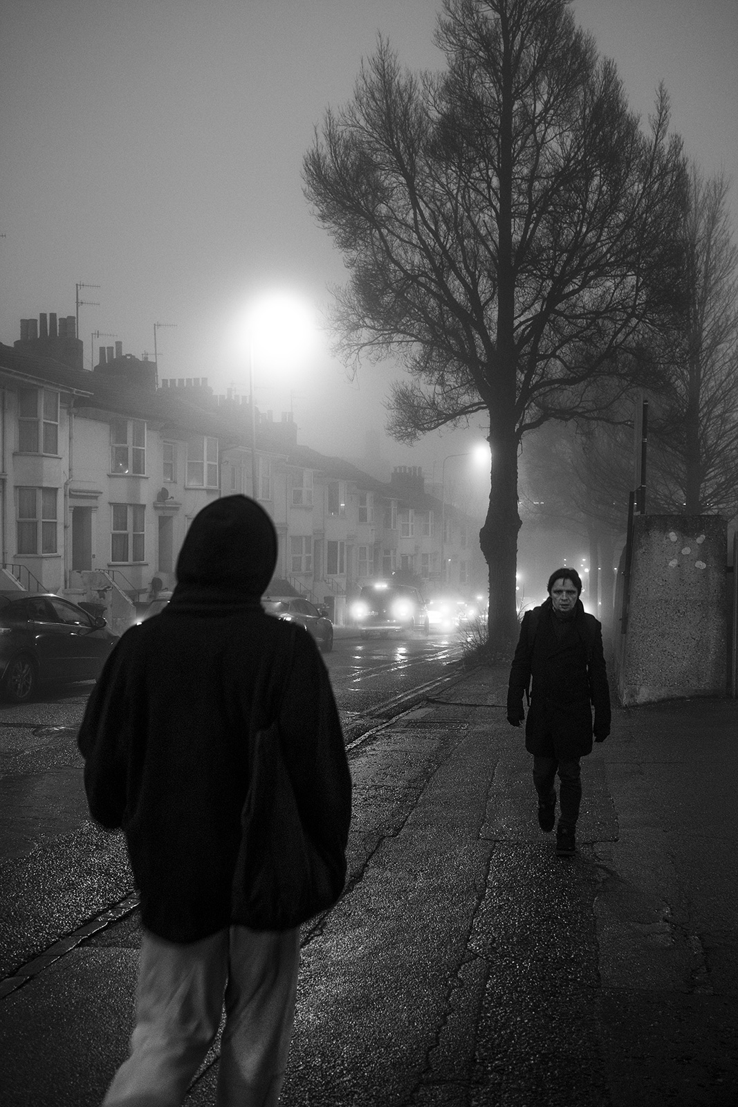 Man walking towards viewer along foggy street at night with silhouetted hooded figure in foreground, black and white documentary street photography portrait Chatham Place Brighton UK © P. Maton 2019 eyeteeth.net