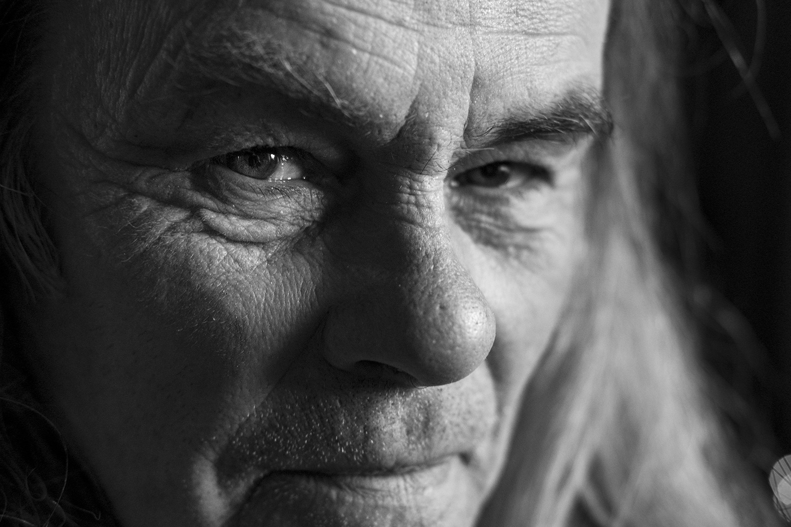 Mature man with shy grin and sparkle in his eye looking at viewer, Marcham Oxfordshire UK black and white landscape portrait with natural light and strong shadows ©P. Maton 2019 eyeteeth.net