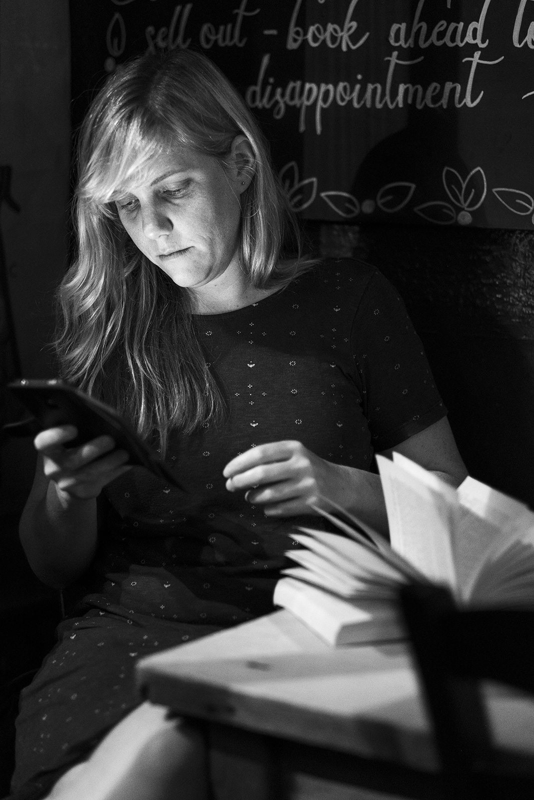 Portrait of young woman lit by glow from her phone screen with open book in foreground at the Shakespeares Head pub in Brighton UK, black and white documentary photograph ©P. Maton 2019 eyeteeth.net