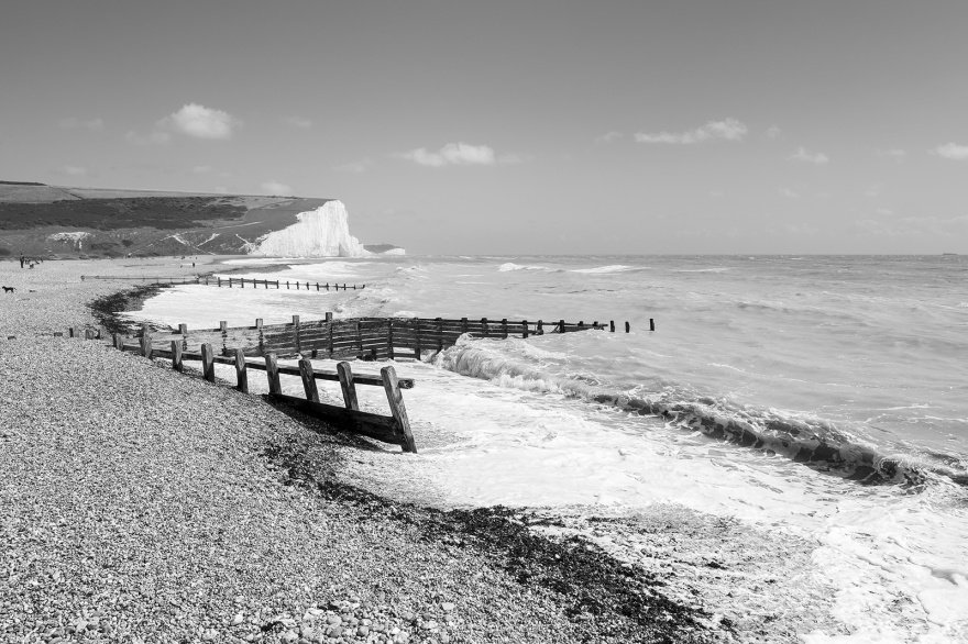 Single beach with sea defences and seven sisters cliffs in background Cuckmere Haven East Sussex UK black and white landscape ©P. Maton 2019 eyeteeth.net