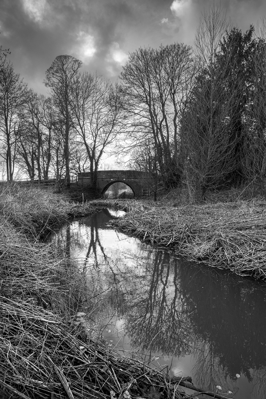 Winter view downstream along river Ouse with bridge and trees at East Sussex UK black and white rural landscape portrait ©P. Maton 2019 eyeteeth.net