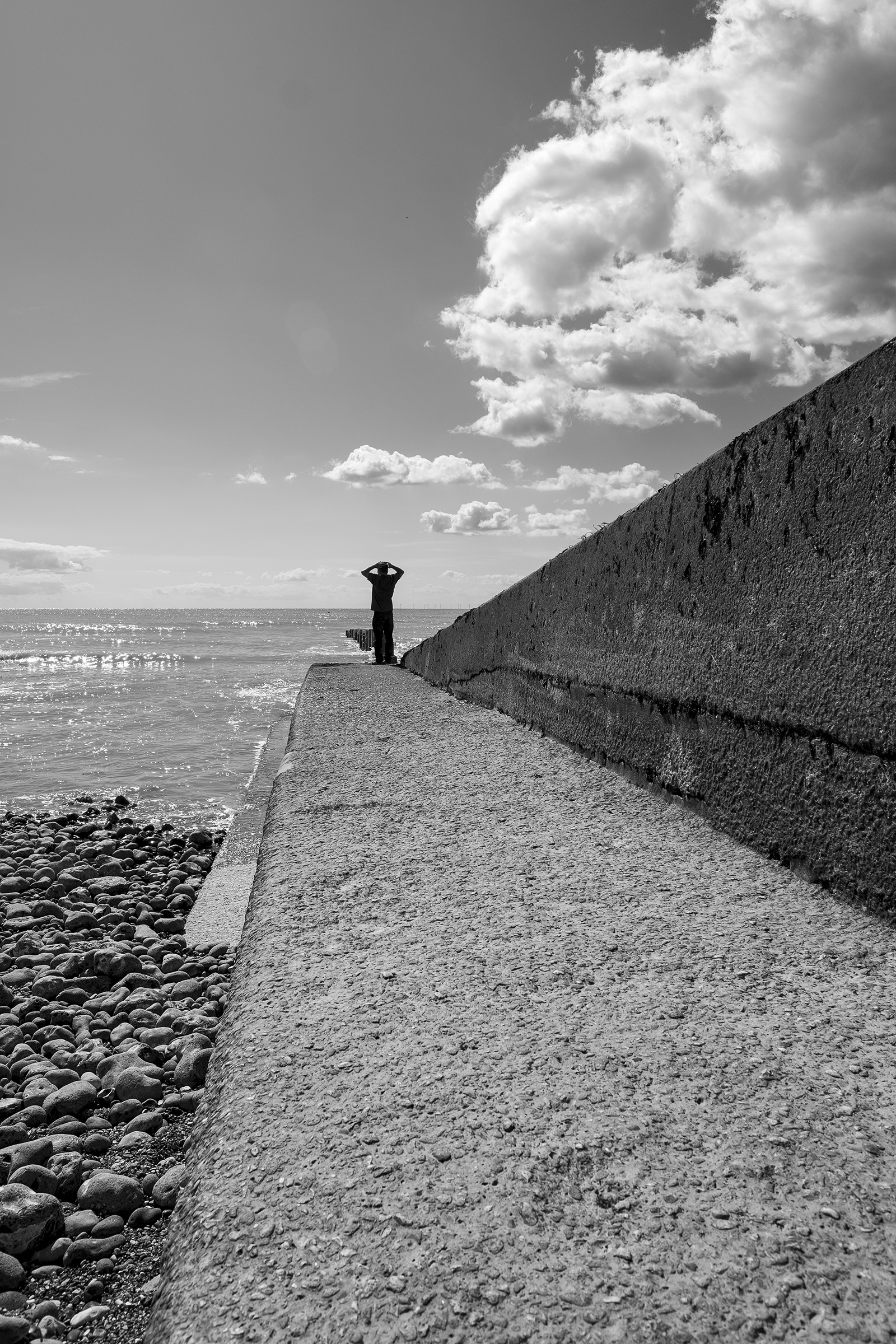 Silhouette of land standing on concrete sea wall groyne with ocean in background Ovingdean East Sussex UK black and white portrait ©P. Maton 2019 eyeteeth.net