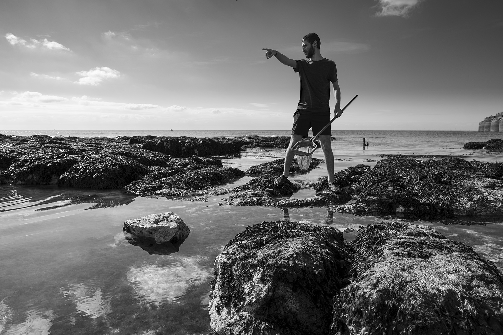 Silhouette of man holding net and pointing standing on on rocks over rock pools with ocean in background Brighton East Sussex UK black and white portrait ©P. Maton 2019 eyeteeth.net