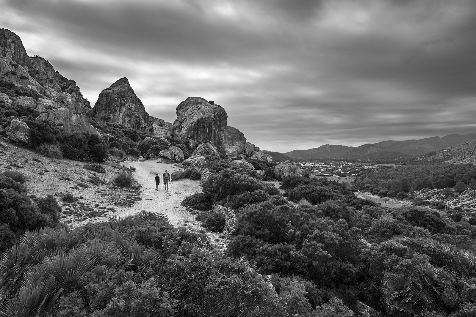 Father and son walking on footpath towards rocky outcrop with view of mountains and Port de Pollenca in background black and white landscape Boquer Valley Mallorca Spain ©P.Maton 2019 eyeteeth.net