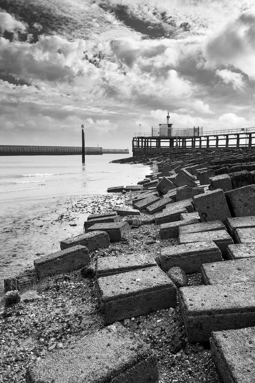 Concrete slabs by harbour arm with harbour mouth in background Sussex UK black and white portrait ©P. Maton 2019 eyeteeth.net