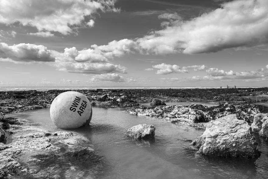 Swim Area Buoy caught in rock pool with dramatic clouds in sky Ovingdean East Sussex UK black and white landscape ©P. Maton 2019 eyeteeth.net